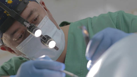 Focus In On Close Up Of Dentist With Mask Working On Patient stock footage