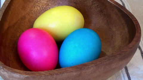 Zoom In Easter Painted Eggs In A Wooden Bowl stock footage