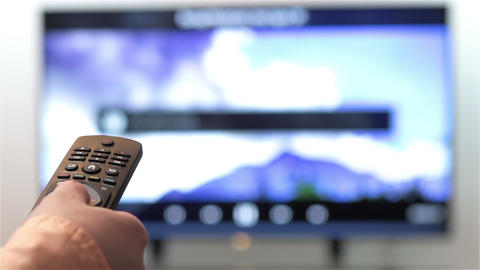 Hand Changes The Channels On Smart TV Remote Control stock footage