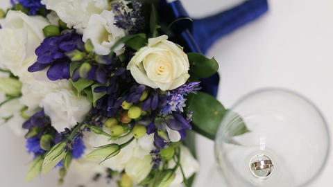 Beautiful bridal bouquet and wedding rings in a glass of wine Footage