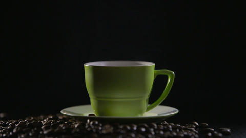 Cup of hot coffee with steam over black background Footage