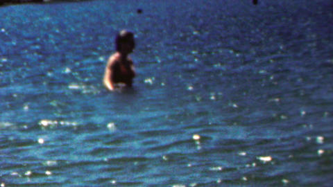 1961: Bikini clad woman wading in deep glistening blue ocean water Footage