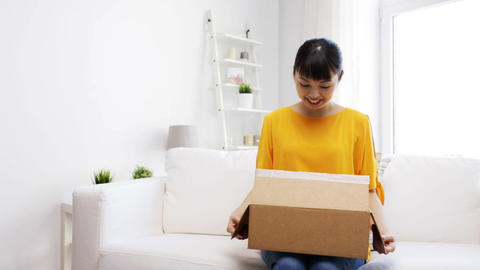 Happy Asian Young Woman With Parcel Box At Home stock footage