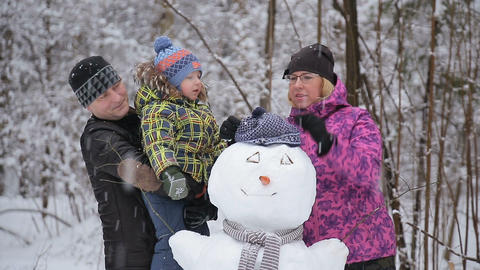 Happy Young Family Playing In Fresh Snow And Building Snowman At Beautiful Sunny stock footage