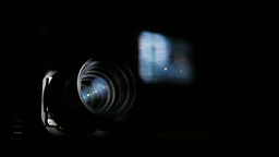Cinema projector lens and blurred movie image on glass, closeup view Footage