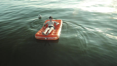 Boy Floating On Air Mattress In The Sea stock footage