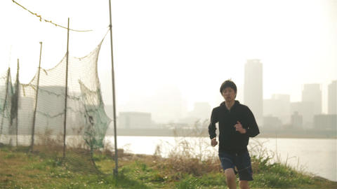 Healthy Young Japanese Runner Running Along Tail Near The Water Overlooking Osak stock footage