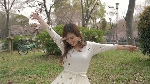 Beautiful Japanese Girl Sitting On The Grass Throwing Leafs In The Air Slow Moti stock footage