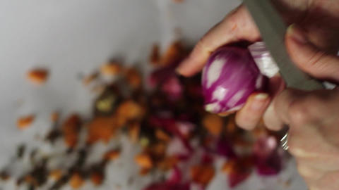 Hands woman cleans a red onion with a kitchen knife 01 Footage