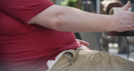 Obese Man Sitting In Park stock footage