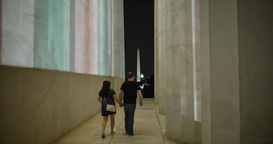 Couple Walks Outside Lincoln Memorial At Night stock footage