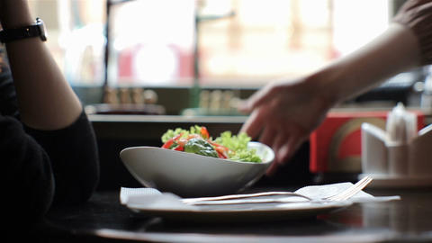 Waiter In A Restaurant Brings A Delicious Fresh Salad Dish To The Table stock footage
