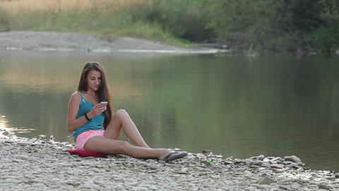 Girl Sitting On The River Bank With The Phone, The Phone Picks stock footage