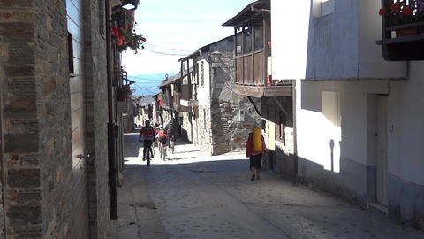 Group Of Bicyclists Going On A Narrow Street Lined By Stone Houses With A Floor  stock footage