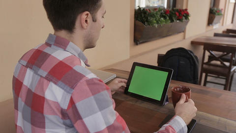 Man Holding Tablet Touch Screen With Green Screen Chroma Key For Custom Content. stock footage