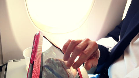 businessman on a passenger plane working with his tablet pc Footage