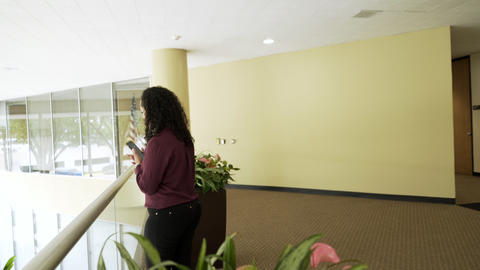 Businesswoman Walks To Interior Balcony Of An Office Building To Use The Cell Ph stock footage