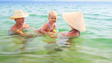 Old Man Mother Lift up Little Daughter Play in Azure Sea Footage