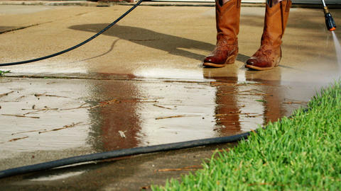 Safety Footwear Used While Pressure Washing Concrete Driveway stock footage