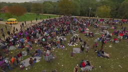 AERIAL VIEW OF SOME 2000 MIGRANTS SITTING IN FIELD stock footage