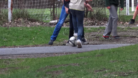 Group Of Youths Playing Football In The Park On A Driveway Where Passing Cyclist stock footage