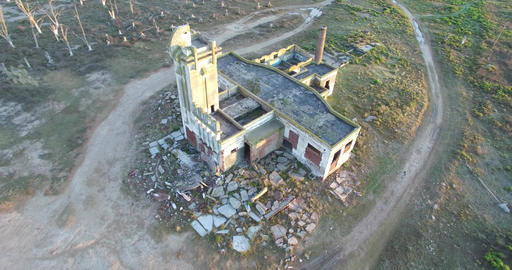 Aerial Drone Scene Of Abandoned Slaughterhouse At Sunset, Surrounded By Dead Tre stock footage