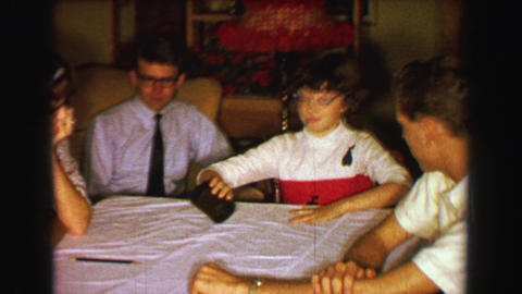 1957: Family playing dice rolling craps gambling game at den table Footage