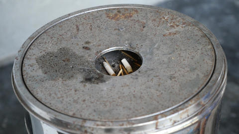 Detail of Male hand Stubbing Out Cigarette in sand ashtray bin Footage