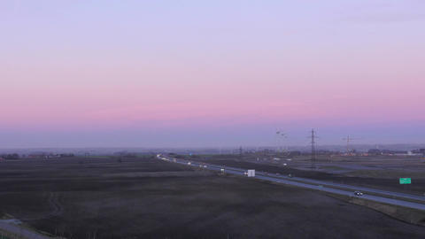 Rural Traffic At Sunset - Wind Farm + Cars stock footage