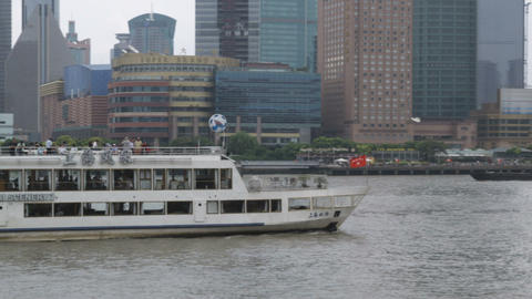Pan of skyscrapers and a passenger boat on the Huangpu River Footage