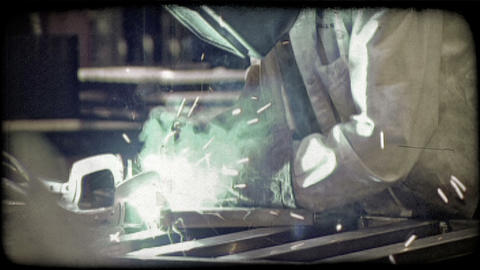 Man Welds In Warehouse. Vintage Stylized Video Clip stock footage