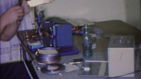 1965: Cinematographer editing table 8mm Super 8 films viewer unwinding reels Footage