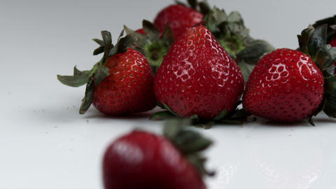 Single Strawberry Rolling Away From The Bunch stock footage