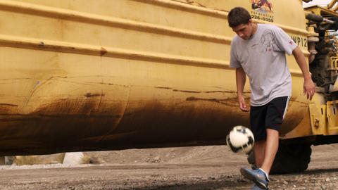 Juggling A Soccer Ball In Front Of A Large Tractor stock footage