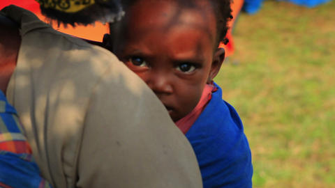 Baby On Mother's Back Looking Into The Camera In Kenya stock footage