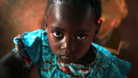 KENYA-C.2012 Little Girl Looks Up At Camera While Recieving A Snack In A Kenya,  stock footage