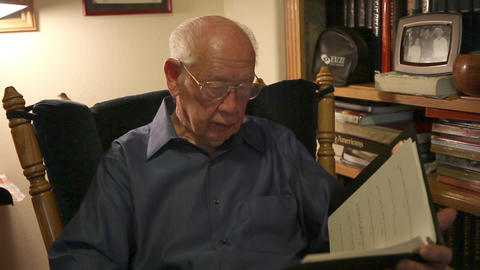 A static shot of an elderly man reading a book in a cozy chair Footage