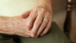 A close up shot of an elderly lady's clasped hands with her wedding ring in view Footage