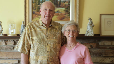 A static shot of an elderly couple standing in front of a picture of nature Footage
