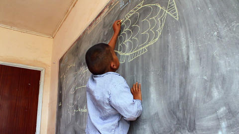 Static shot of young boy drawing on chalkboard Footage