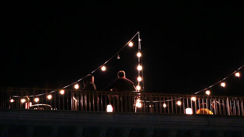 View Of People On A Deck Outside At Night With Lights Strung Up Around stock footage