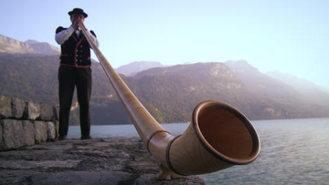 Low-angle Footage Of Man Playing Alphorn Next To Lake stock footage