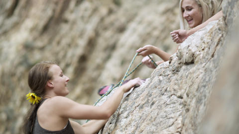 Rock Climbing Woman, Helped To The Top By Her Friends stock footage