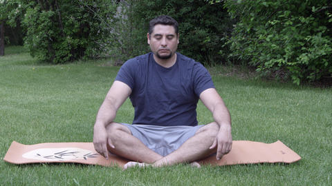 Man On Yoga Man In Grass Rotating Neck And Arm Joints stock footage