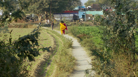 Two Women Walk Down Dirt Path In Bright Colored Saris stock footage