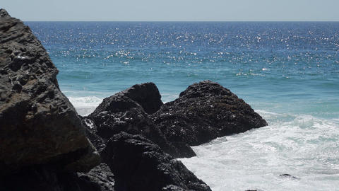View of waves hitting rocks on a sunny day at Point Dume Footage