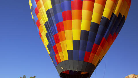 Tilting Shot Of A Colorful Hot Air Balloon With Passengers Aboard, Preparing To  stock footage