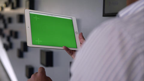 View Over The Shoulder Of Person Using Tablet With Green Screen stock footage
