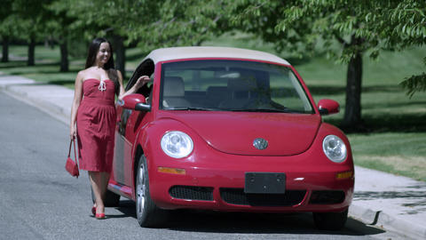 Slow Motion Of Woman In Red Dress Walking And Posing Next To Red Volkswagon Bug stock footage