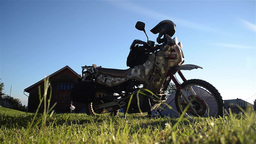 Motorcycle sitting at rest in a field where the grass is beaten by wind 13 Footage